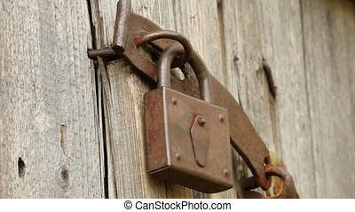 A woman opens a nail old padlock on a shed