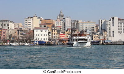 a ferry boat pulls into port, with the galata tower in the background, istanbul, turkey