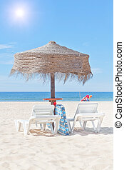 Wooden beach umbrella and sun bed on the beach, in the...