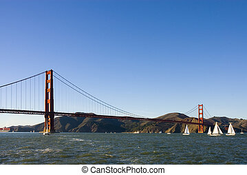 Golden gate bridge from a boat, with sail boats in the bay