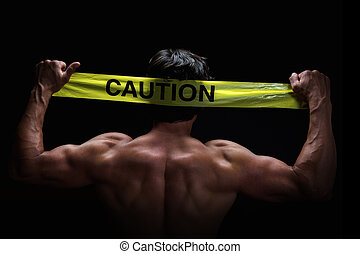 Caution - Attractive young man flexes his muscles whilst...