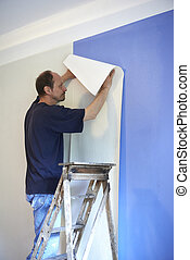 man putting up wallpaper