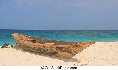 zanzibar boat on a tropical beach - fishing boat lie down on...