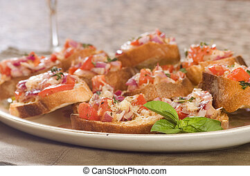 Plate of fresh bruschetta with a sprig of mint
