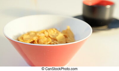 breakfast with flakes and milk - pouring corn flakes and...