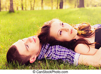 Young happy couple resting on the grass