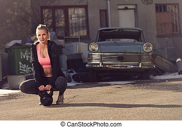 Fitness Woman with Kettlebell on the Street Resting