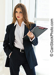 Businesswoman in man's suit & shirt writing with pen at her...