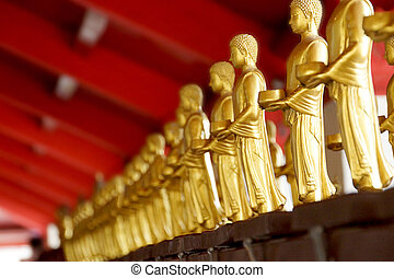 Nakhon Si Thammarat THAILAND-May 09: A row of standing Buddhas holding monk s alms-bowls at the temple of Wat Phra Mahathat on may 09, 2013 in Nakhon Si Thammarat Thailand