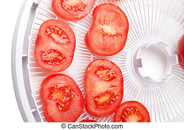 Fresh tomato on food dehydrator tray ready to dry Isolated...