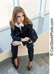 Young business woman wearing man's suit sitting on stairs