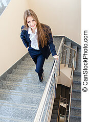 Young business woman wearing man's suit walking on stairs
