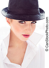 Headshot of young business woman wearing man's shirt, hat in office