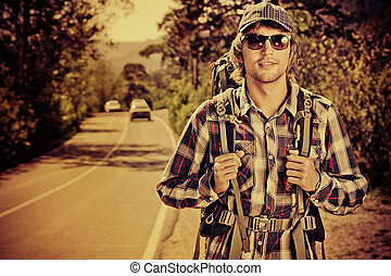 car catcher - Young man tourist hitchhiking along a road.