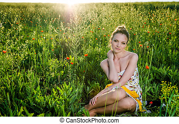 young Woman relax in poppy field, sunset