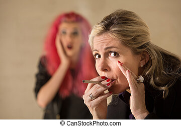 Woman Sneaking a Cigarette - Surprised teen behind mature...