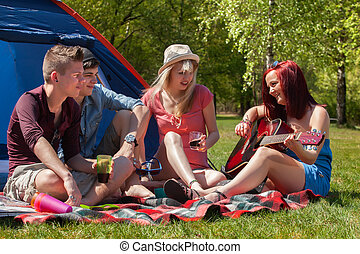 Playing music on a camping - Young teenager group are having...