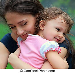 Happy mother and daughter cuddling outdoor green background....