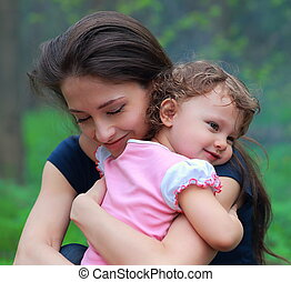 Smiling happy mother and cute kid girl cuddling outdoor summer background. Closeup tender and love portrait