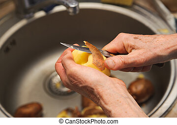 Elderly woman to peel potatoes. Kitchen working. Prepare...
