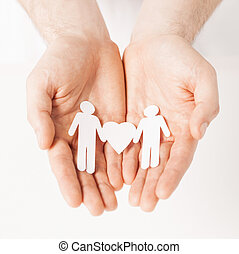 man hands with paper men - mans hands showing two paper men...