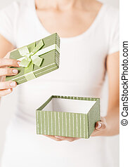 woman hands with gift box - close up of woman hands opening...