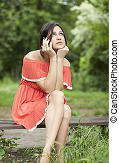 girl in the park - beautiful girl in a red dress sitting on...
