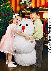 Happy Christmas - two beautiful child and toy snowman near...