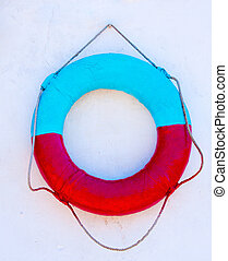 lifebuoy - red and blue life ring hanging on a white wall
