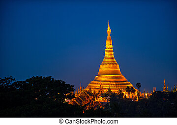 Shwedagon Pagoda Temple with village below in the twilight...
