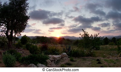 timelapse of the sun setting over a garden in the hills of...