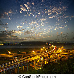 Highway in night with cars light in modern city in Taiwan,...