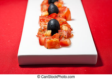 Italian amuse buche - Choped tomatos, basil and black olive...