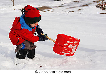 Helping out - a young boy shovels snow with a toy shovel