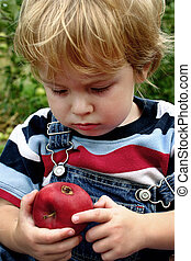 A bad apple - Toddler boy scowls at a bad spot in an apple