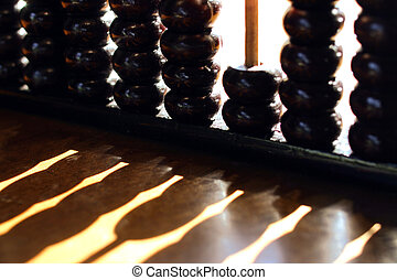 Shadows - Close up of an abacus that is casting a shadow on...
