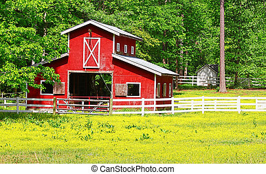 An unusual two story old red horse barn outside among the...