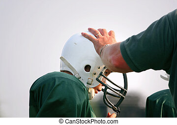 Hands on coaching - The coach is explaining a play to one of...