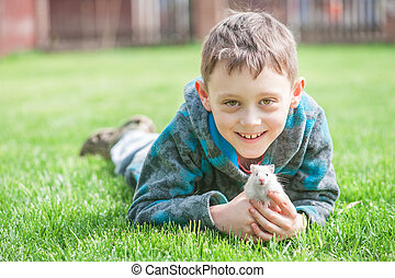 hamster - boy with white hamster on lawn closeup
