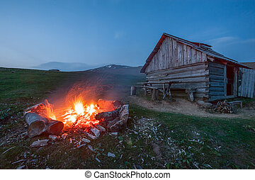 campfire in mountain near hunting house
