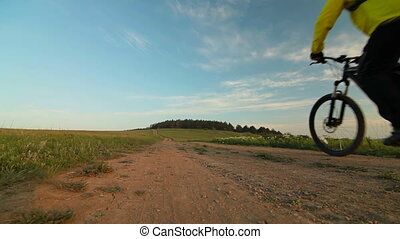 Man riding bicycle through a field in the morning. Rear...
