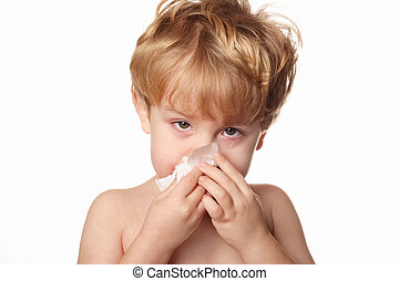 sick child wiping his nose - A sick young boy wiping his...