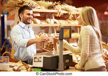 Buying - Young girl in a bakery