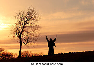 Praise - Silhouette of a man on a hill standing by a tree...