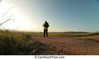Man hiking through morning field