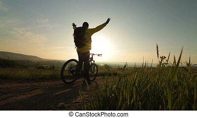 Cycling towards the sun - Biker silhouette at sunrise, arms...