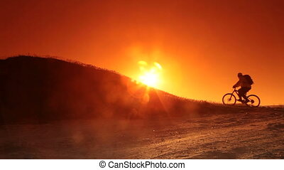 Cyclist riding bicycle into sun - Silhouette of cyclist...