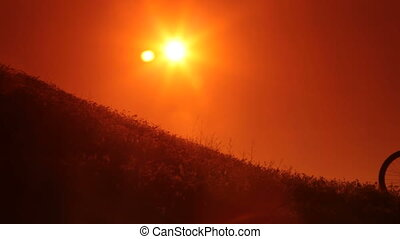 Mountain Biking At Sunset - Silhouette of cyclist riding...