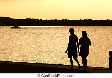 Stroll by the Lake - Two people walk along the shore of a...