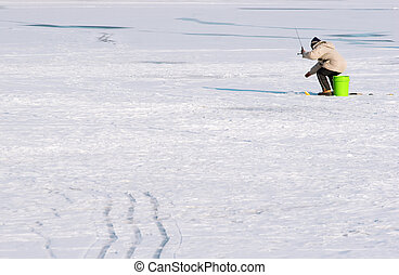 Ice Fishing - A person sits on a bucket on a frozen lake...